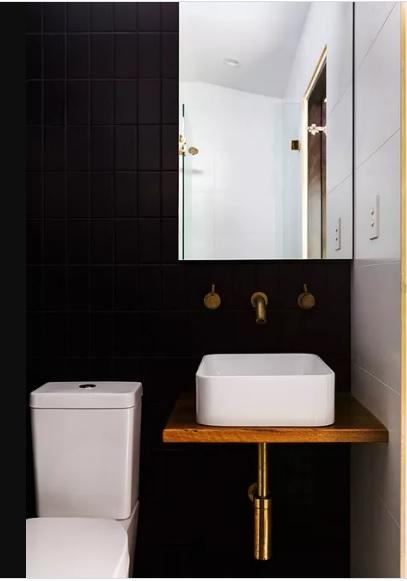 Phòng tắm màu đen với đồng thau